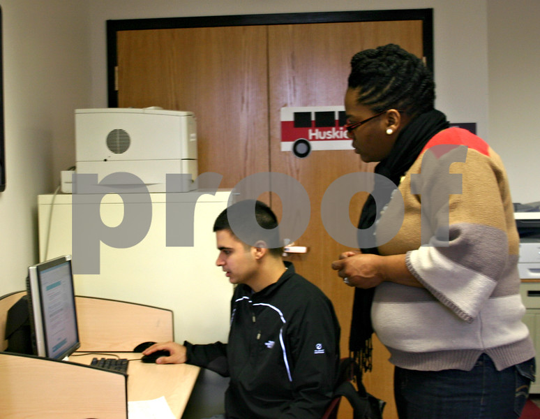 Nikkita Carrington, student service coordinator at Northern Illinois University's Student Financial Aid Office, helps freshman Ulises Pico fill out a Free Application for Federal Student Aid during FAFSA Friday's.<br /> <br /> By Nicole Weskerna - nweskerna@shawmedia.com