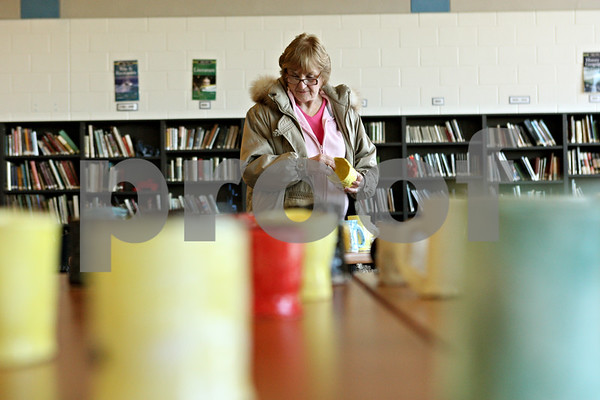 Rob Winner – rwinner@shawmedia.com<br /> <br /> On Friday, March 9, Genoa resident Joanne Burrows looks over a table covered with mugs and bowls for sale that were made by Genoa-Kingston students in their art fundamentals class. Profits made by the sale will be split between the art department and Hope Haven. Burrows is a former teacher of G-K High School.