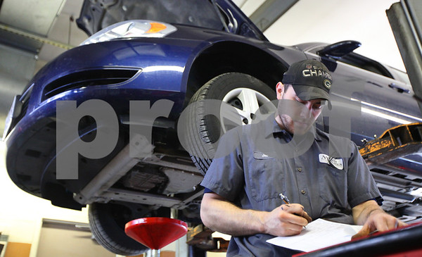 Kyle Bursaw – kbursaw@shawmedia.com<br /> <br /> While doing an oil change on a Chevy Impala, Motor Works Technician Joe Moberg marks off parts of an inspection checklist for the vehicle on Wednesday, Jan. 4, 2012.