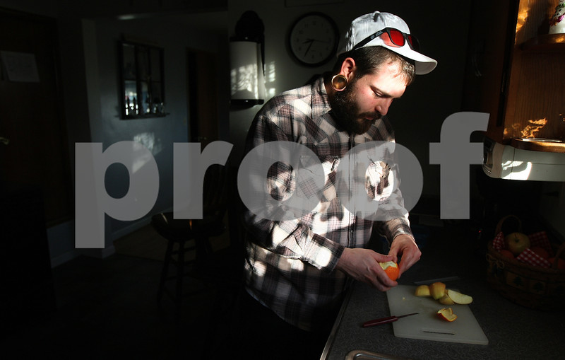 Kyle Bursaw – kbursaw@shawmedia.com<br /> <br /> Matt Jordan peels an orange in his parents' kitchen while prepping his lunch for work on Friday, Dec. 16, 2011.