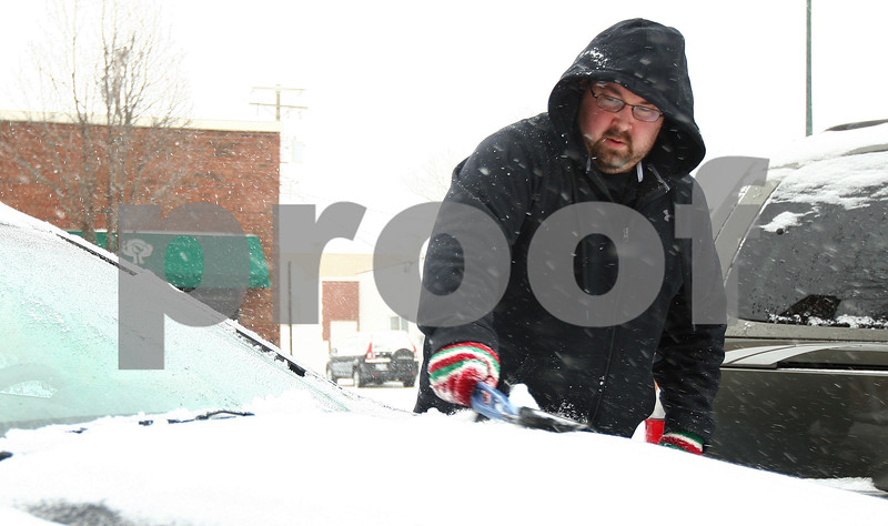 Kyle Bursaw – kbursaw@shawmedia.com<br /> <br /> Sycamore resident Andy Vanatta brushes snow off his car parked on South Maple Street in Sycamore, Ill. on Thursday, Jan. 12, 2012.