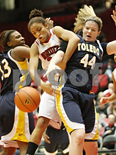 Rob Winner – rwinner@shawmedia.com<br /> <br /> Northern Illinois' Kim Davis (center) and Toledo's Kyle Baumgartner (44) look to control a loose ball under the Huskies' basket during the second half in DeKalb on Saturday afternoon. Toledo defeated NIU, 49-47.