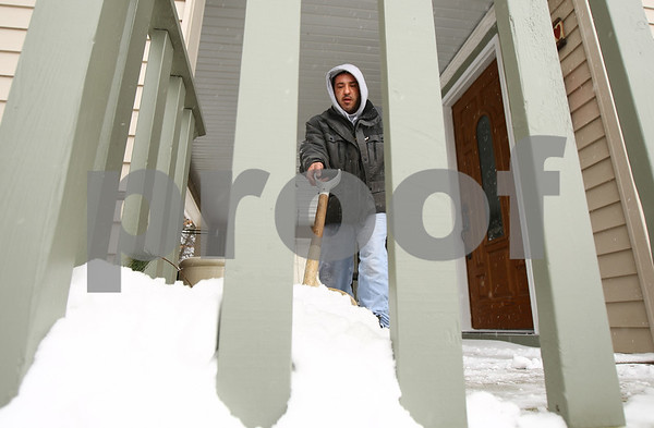 Kyle Bursaw – kbursaw@shawmedia.com<br /> <br /> Sam Pappas shovels the snow off of the porch area of a Sycamore business on Somonauk Street on Thursday, Jan. 12, 2012. Pappas has a lawn care and snow removal business based in DeKalb.