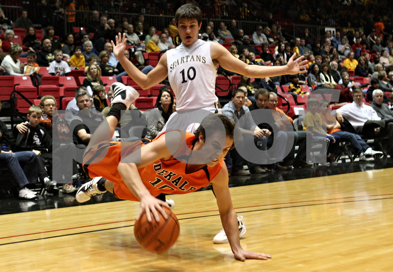 Rob Winner – rwinner@shawmedia.com<br /> <br /> DeKalb's Brian Sisler (front) goes to the floor after a foul by Sycamore's Brandon Spartz-Raikes during the third quarter. DeKalb defeated Sycamore, 57-41, at the Convocation Center in DeKalb on Friday night.