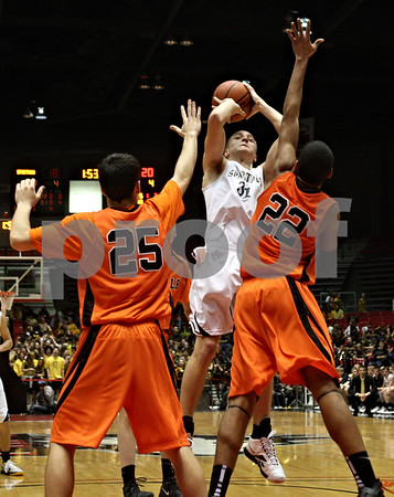 Rob Winner – rwinner@shawmedia.com<br /> <br /> Sycamore's Thomas Paulson (31) takes a shot as DeKalb's Kyle Berg (25) and Andre Harris (22) defend during the second quarter.