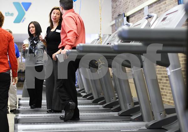 "Kyle Bursaw – kbursaw@shawmedia.com<br /> <br /> YMCA employees (from left) Rachel Beach, Katrina Luetkebuenger and Charlie Irick talk on the treadmills at the grand opening of the new satellite site dubbed ""DeKalb Barb City YMCA at Huntley Middle School"" on Thursday, Jan. 19, 2012."