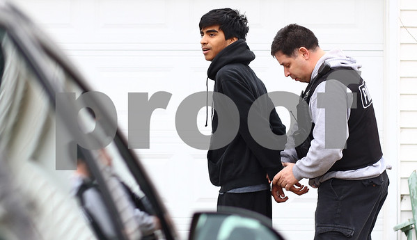 Kyle Bursaw – kbursaw@shawmedia.com<br /> <br /> Detective Angel Reyes, of the DeKalb Police Department, handcuffs Matthew Zamudio in front of his residence on Thursday, Feb. 23, 2012. Zamudio, who was arrested for delivery of marijuana, was just one arrest of several drug-related arrests throughout the day.