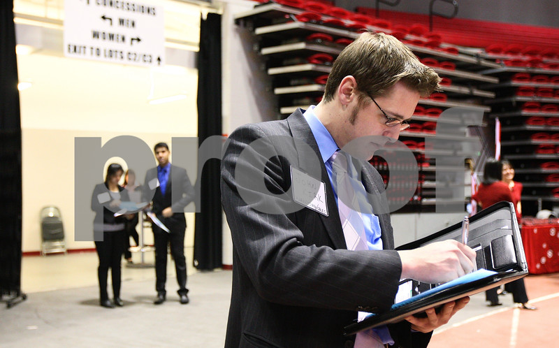 Kyle Bursaw – kbursaw@shawmedia.com<br /> <br /> John Kirk, a senior majoring in marketing and sales at NIU, looks over a list of employers at the internship fair held in the Convocation Center on Tuesday, Feb. 21, 2012.