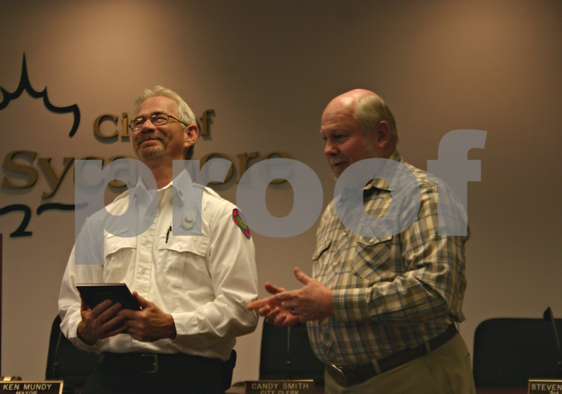 Jeff Engelhardt – jengelhardt@shawmedia.com<br /> Retiring Sycamore Fire Chief Mark Kessler (left) laughs as Mayor Ken Mundy gives him advice for his life in retirement during a ceremony Friday at city hall.