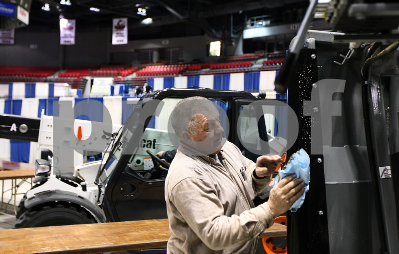 Kyle Bursaw – kbursaw@shawmedia.com<br /> <br /> Dennis Mottl, from the Dubas Cattle Company, wipes down a hydraulic squeeze chute, one of his company's products, as he sets up for the farm show in the Convocation Center on Tuesday, Jan. 10, 2012.