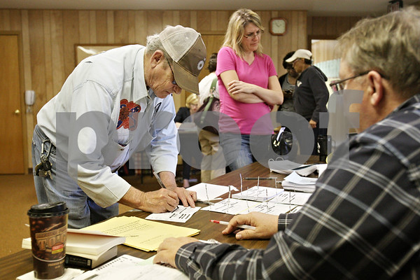 Rob Winner – rwinner@shawmedia.com<br /> <br /> Voters including Frank Meadows (left) sign in before receiving his ballot at the Cortland Township Building on Tuesday afternoon.