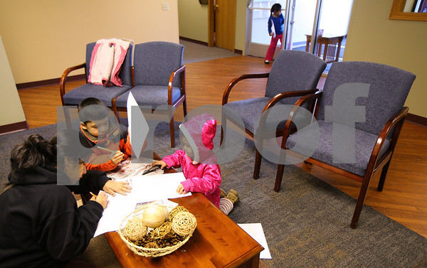 Kyle Bursaw – kbursaw@shawmedia.com<br /> <br /> Quirina Hernandez (bottom left) fills out a form in the new waiting area of the District 428 office, while her children (from left) Jose, Shalane and Estehefane   Rodridguez draw and explore in the area on Monday, Jan. 9, 2012. The wood flooring in the area came from leftover materials from Cortland Elementary.