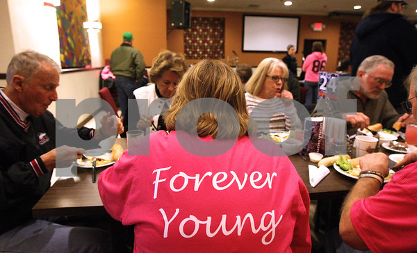 Kyle Bursaw – kbursaw@shawmedia.com<br /> <br /> Lexi Weber's grandmother Rita Johnson (center) as well as other family members wear pink shirts from another event honoring Weber and Tim Getzelman during the community meal also honoring the couple at Feed 'Em Soup on Wednesday, Feb. 29, 2012. The front of the shirts have a picture of the pair and the back simply reads 'Forever Young.'