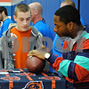 Chicago Bears linebacker Nick Roach signs a football for Austin Arndt, 14, of DeKalb, Saturday, Jan. 14, at Genoa-Kingston High School. His appearance was part of a fundraiser for the Genoa-Kingston Wrestling Club.<br /> <br /> By Nicole Weskerna - nweskerna@shawmedia.com