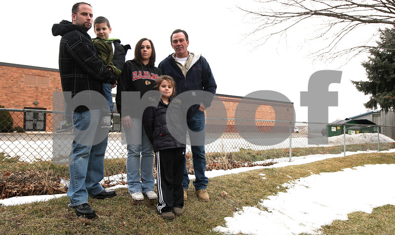 Kyle Bursaw – kbursaw@shawmedia.com<br /> <br /> Bob and Danielle Barnett, their two kids Nathan (in Bob's arms) and Debra (front) and Danielle's father Dan Olita (at right) and have had their basement on South Hadsall street flooded multiple times. The berm on the property (which they're pictured standing on) was unable to stop the flooding alone and Genoa Elementary (in background) put in a swale to help prevent further flooding, but the family and neighbors were asking them to do this years ago.<br /> <br /> Taken Friday, Feb. 3, 2012.