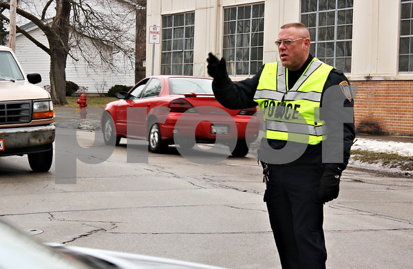 ANDREW MITCHELL — amitchell@shawmedia.com<br /> DeKalb Police officer Kent Quist directs traffic Wednesday at the intersection of Pearl and Gurler Streets. Traffic was backed up with motorists looking for a way around a stalled freight train in downtown DeKalb.