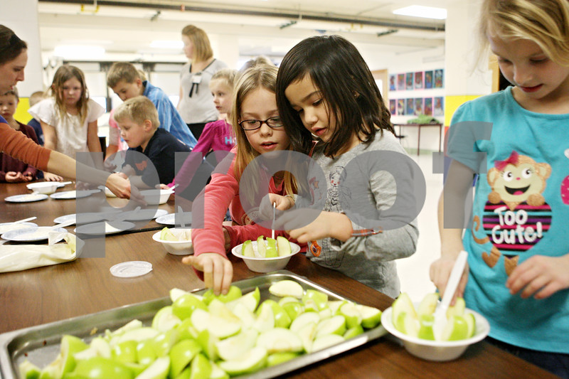Rob Winner – rwinner@shawmedia.com<br /> <br /> (From left to right) Darla Thorn, 9, Nika Gutierrez, 6, and Amanda Grant, 6, prepare themselves a yogurt and apple snack during an after-school CATCH Program at Southeast Elementary School in Sycamore on Tuesday, Jan. 10, 2012. CATCH stands for a Coordinated Approach To Child Health and is a coordinated school health program designed to promote physical activity, healthy food choices and the prevention of tobacco use in children.