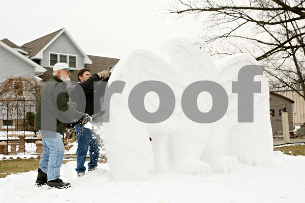 Rob Winner – rwinner@shawmedia.com<br /> <br /> Lynden Bute (left) is helped by Mike Boddy as the two create a snow sculpture featuring an American bald eagle outside Bute's home in Sycamore on Wednesday afternoon.<br /> <br /> Wednesday, Jan. 25, 2012<br /> Sycamore, Ill.
