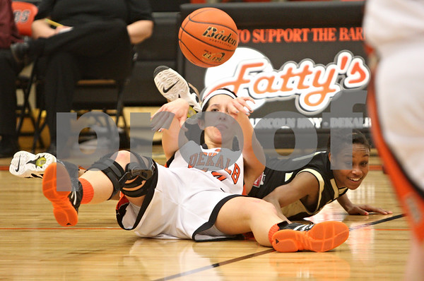 Rob Winner – rwinner@shawmedia.com<br /> <br /> DeKalb's Rachel Torres (left) passes the ball after a steal attempt by Sycamore's Lake Kwaza during the fourth quarter in DeKalb on Thursday, Feb. 9, 2012.