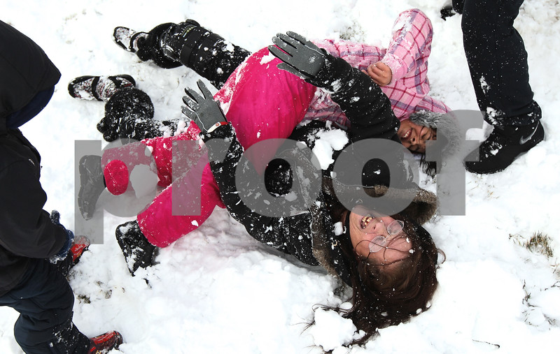 Kyle Bursaw – kbursaw@shawmedia.com<br /> <br /> Joann Blough wrestles in the snow with niece Breiona Mendez (top) as Blough's grandson Liam Kaemke (left) and nephew Brandyn Rosario (right) ambush the pair with snowballs in front of Liam's home in DeKalb, Ill. on Friday, Feb. 24, 2012. Blough said she decided to come over and build snowmen with the kids when she heard school was canceled, but it evolved into a snowball fight.