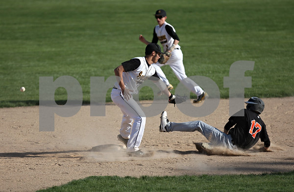 Rob Winner – rwinner@shawmedia.com<br /> <br /> Sycamore shortstop Jordan Mitchell (left) can't find the handle on a ball as DeKalb baserunner Tyler Gosnell (17) slides safely into second base during the top of the third inning Thursday in Sycamore. DeKalb defeated Sycamore, 9-2.