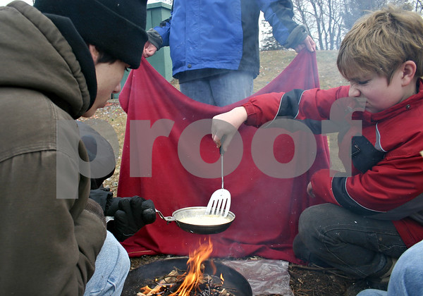 On the right, Eddie Deja, 12, tries to flip a pancake as Ian Lovell, 15, holds a small skillet over a fire built by Sycamore Boy Scout Troop 2 on Saturday, Feb. 4, 2012.<br /> <br /> By Nicole Weskerna - nweskerna@shawmedia.com
