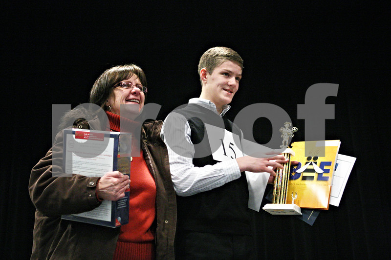 """Rob Winner – rwinner@shawmedia.com<br /> <br /> Carole Rydecki (left) stands on stage with her son Ben Rydecki, 14 of Somonauk Middle School, after Ben won the DeKalb County Spelling Bee at Kishwaukee College on Saturday, Feb. 25, 2012. """"Oratorio"""" was the winning word of the spelling bee which lasted 14 rounds."""