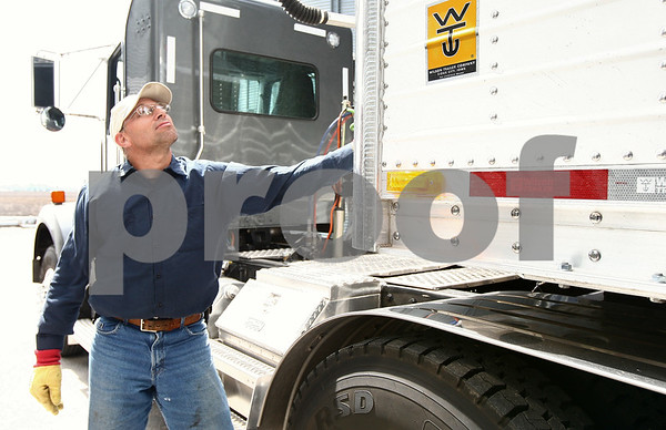 Kyle Bursaw – kbursaw@shawmedia.com<br /> <br /> Mark Neff, a long-time employee on Tracy Jones' farm, uses the controls to put the cover back onto a truck after filling it with corn  on Tuesday, March 27, 2012.