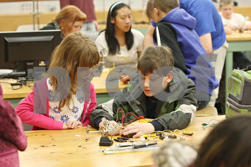 Rob Winner – rwinner@shawmedia.com<br /> <br /> Cheyenne Fischer-Zimmermann (left), 10 of Bloomingdale, and Connor McGinnis, 10 of Elburn, use a voltage meter to measure the electricity produced from a battery pack during a hands-on basic circuitry class presented by the Northern Illinois University STEM Outreach program on Saturday morning on the NIU campus in DeKalb. STEM stands for science, technology, engineering and math.
