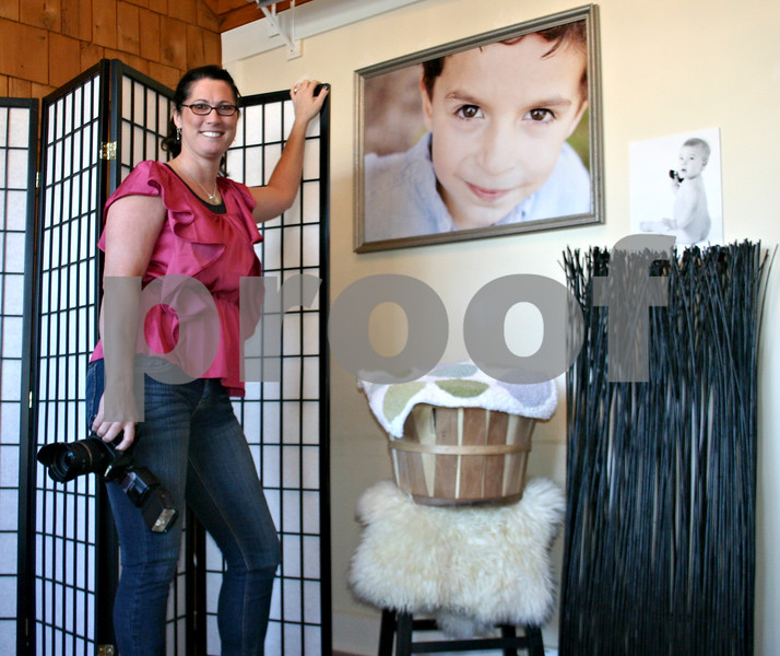 Erica Scalf Photography opened its doors last week in Genoa. Pictured is owner Erica Scalf at her new studio next to a few of her portraits.<br /> <br /> By Nicole Weskerna - nweskerna@shawmedia.com