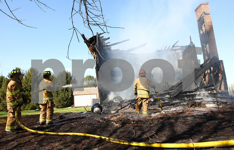 Kyle Bursaw – kbursaw@shawmedia.com<br /> <br /> Leland firefighters (from left) Jim Barnes, Fred Seville and Tim Nelson work to extinguish what's left of a building at 3159 Graham Rd in Somonauk, Ill. on Wednesday, March 28, 2012. Homeowner Michael Hamer said he has been grilling out about an hour before his meeting, and said that possibly is where the fire started.