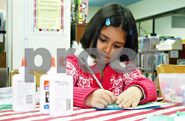 Nicole Weskerna – nweskerna @shawmedia.com<br /> <br /> Emma Cohen, 6, of DeKalb creates a New Year's resolution tree at the DeKalb Public Library on Saturday. Once she finished coloring the tree, she and her family were able to fill the branches with their resolutions for 2012.