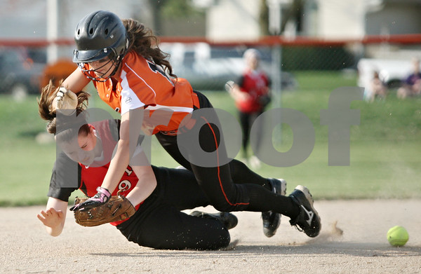 Rob Winner – rwinner@shawmedia.com<br /> <br /> While trying to field a ground ball, Huntley shortstop Miranda Peterson (bottom) collides with DeKalb base runner Hannah Walter during the bottom of the first inning in DeKalb on Wednesday. Walter was called out on the play for interference.