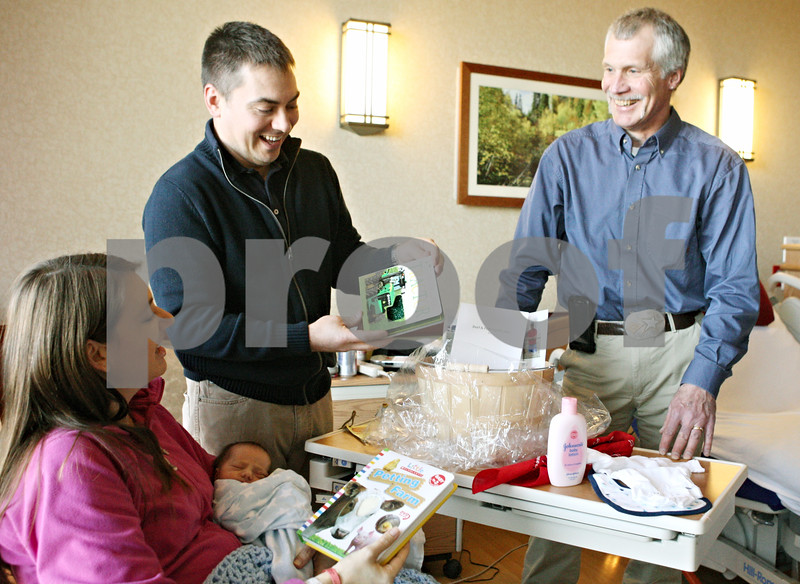 Rob Winner – rwinner@shawmedia.com<br /> <br /> Roger Faivre (right) delivers a gift basket filled with an assortment of agriculture related products to new parents Amanda and Matt Brown for their baby Charles at Kishwaukee Community Hospital in DeKalb on Friday. Faivre, a local farmer, was delivering the basket as part of National Agriculture Week. Charles Brown was born Thursday morning weighing 5 pounds, 13 ounces and 19 inches.