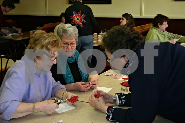 Shirley Gylleck of Genoa (right) shows Joanne Burrows (left) and Judy Hodge (center), both of Genoa, how to do a needle turn appliqué with a fabric heart at the Needle Workers' Delight at Genoa Café on West Main Street in Genoa. The event, which offered a meal and the choice of five sewing or quilting projects, was part of the Quilt and Fiber Arts Walk, which began Jan. 25 and ended Sunday.<br /> <br /> Caitlin Mullen - cmullen@shawmedia.com