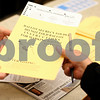 Kyle Bursaw – kbursaw@shawmedia.com<br /> <br /> Election Judge Sharon Holmes (left) hands off a blank primary ballot to a voter on the first day of early voting in the Legislative Center in Sycamore, Ill. on Thursday, Feb. 9, 2012.