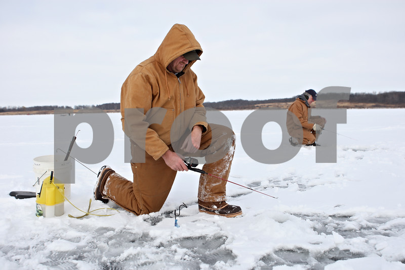 Rob Winner – rwinner@shawmedia.com<br /> <br /> Mike Sitarski (front), of Batavia, and his brother Rich Sitarski, of Roselle, try their luck ice fishing at Shabbona Lake in Shabbona on Saturday afternoon. Saturday was the 1st Night Ice Fishing Event sponsored by Cabela's at Shabbona Lake.