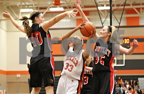 Rob Winner – rwinner@shawmedia.com<br /> <br /> DeKalb's Courtney Patrick (33) drives to the basket as Huntley's Samantha Andrews (40) and Abbey Shaw (35) defend in the first quarter during the Class 4A DeKalb Regional final on Thursday, Feb. 16, 2012. DeKalb defeated Huntley, 55-40.