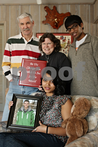 """Rob Winner – rwinner@shawmedia.com<br /> <br /> Kevin Ballantine's family including his father Dave Ballantine (from left to right), mother Diane DeMers, sister Pooja Ballantine and brother Keerti Ballantine are seen in their DeKalb home on Saturday afternoon. Kevin Ballantine, 23, died in January after a long battle with leukemia. Before he passed away, family and friends wrote letters to Ballantine that expressed how he touched their lives, which his mother Diane collected and placed them in a red binder with the words """"Be The Change You Wish To See In The World"""" on the cover."""