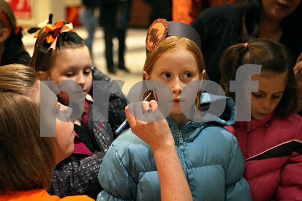 Rob Winner – rwinner@shawmedia.com<br /> <br /> Abby Sipes (left) applies face paint to DeKalb fan Ava Carlson, 8, at the Convocation Center in DeKalb before the start of the DeKalb and Sycamore basketball games on Friday night.