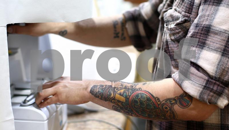 Kyle Bursaw – kbursaw@shawmedia.com<br /> <br /> Jordan, who has multiple tattoos, runs a machine at Accu-Lab in Sycamore, Ill, where he makes prescription glasses on Friday, Dec. 16, 2011.