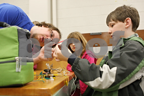 Rob Winner – rwinner@shawmedia.com<br /> <br /> Instructor Jeremy Benson (from left) helps Cheyenne Fischer-Zimmermann, 10 of Bloomingdale, and Connor McGinnis, 10 of Elburn, with a small fan powered by a battery pack during a hands-on basic circuitry class presented by the Northern Illinois University STEM Outreach program on Saturday morning on the NIU campus in DeKalb. STEM stands for science, technology, engineering and math.