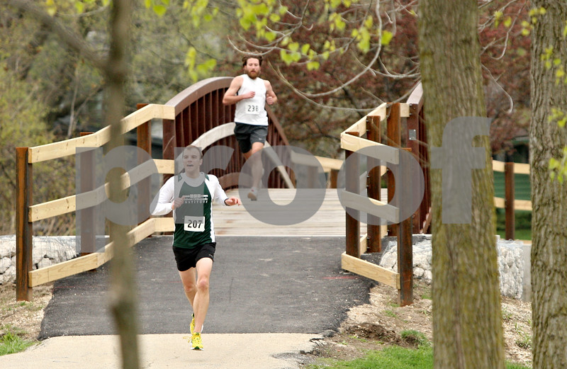 Rob Winner – rwinner@shawmedia.com<br /> <br /> David Gramer (left) of Cortland and Nathan Eagen of DeKalb cross a bridge over the Kishwaukee River during the second annual Hustle for Hearing 5K run/walk Saturday morning at Hopkins Park in DeKalb. Gramer finished the race first and Eagen second. The Student Academy of Audiology hosted the event with RAMP's Deaf and Hard-of-Hearing chosen as the beneficiary of the event.