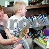 Kyle Bursaw – kbursaw@shawmedia.com<br /> <br /> Aidan Cooper, 4, hops off, his mother, Colleen Cooper's lap to go get another book for her to read to him at the Kirkland Public Library on Thursday, March 22, 2012.
