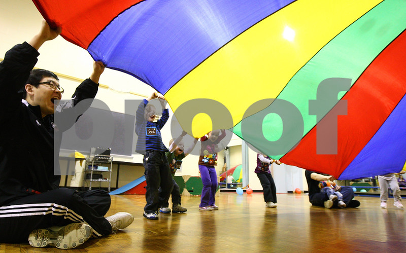 Kyle Bursaw – kbursaw@shawmedia.com<br /> <br /> Graduate Assistant Junhyung Baek (left) and children in the NIU Motor Development Research Program play a game with a parachute in Anderson Hall on Wednesday, Feb. 22, 2012. The program has a Kinesiology class working with young children to develop their motor skills.