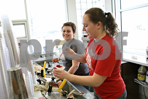 Rob Winner – rwinner@shawmedia.com<br /> <br /> Courtney Olson (front) and Laura Erickson work together making frozen treats at Ollie's Frozen Custard in Sycamore on Wednesday afternoon. Ollie's opens the last Wednesday in February every year.