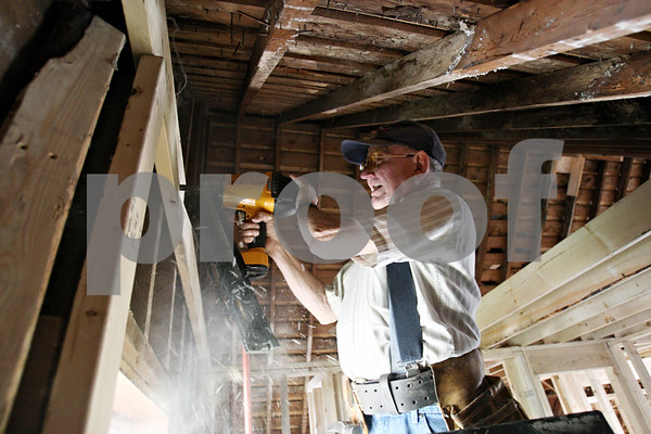 Rob Winner – rwinner@shawmedia.com<br /> <br /> Chuck Janssen, of Genoa, uses a nail gun to secure a ceiling joist as Habitat for Humanity of DeKalb County work on the rehab of a home at 615 Roosevelt Court in Sycamore on Saturday.