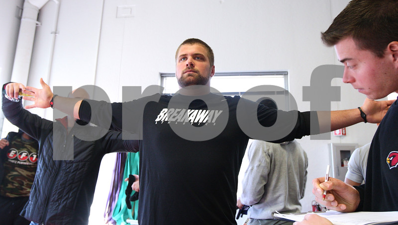 Kyle Bursaw – kbursaw@shawmedia.com<br /> <br /> A scout from the Arizona Cardinals looks on as former Northern Illinois center Scott Wedige is measured in the weight room of the Yordon Center during the NIU Pro Day on Friday, March 9, 2012.