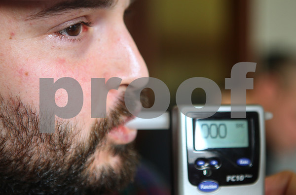 Kyle Bursaw – kbursaw@shawmedia.com<br /> <br /> Matt Jordan blows into a breathalyzer held by drug court coordinator Marilyn Stromborg on Friday, March 16, 2012 after being in drug court. Jordan and others in the program have to call in every day before 8:30 a.m. throughout the duration of their time in drug court to see if he has to go to the courthouse for a random drug test.