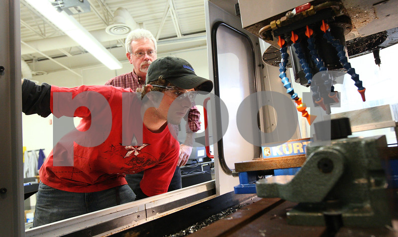 """Kyle Bursaw – kbursaw@shawmedia.com<br /> <br /> Rich Nelson, 21, calibrates a machine in his computer-aided manufacturing class as instructor Bob Lawrence looks on at Kishwaukee College on Wednesday, April 4, 2012. Nelson started learning about manufacturing when he took classes at the college for two years through the Kishwaukee Education Consortium program while a student a Genoa-Kingston High School. """"[The KEC program] got me ready for this, its a perfect start,"""" said Nelson who works at Sycamore Precision."""